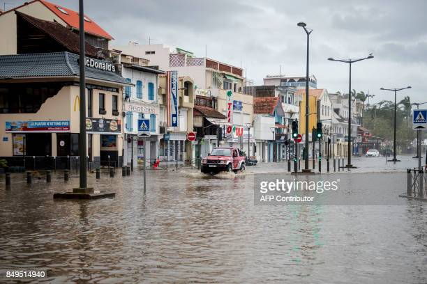 TOPSHOT A motorist drives on the flooded waterfront in FortdeFrance on the French Caribbean island of Martinique after it was hit by Hurricane Maria...