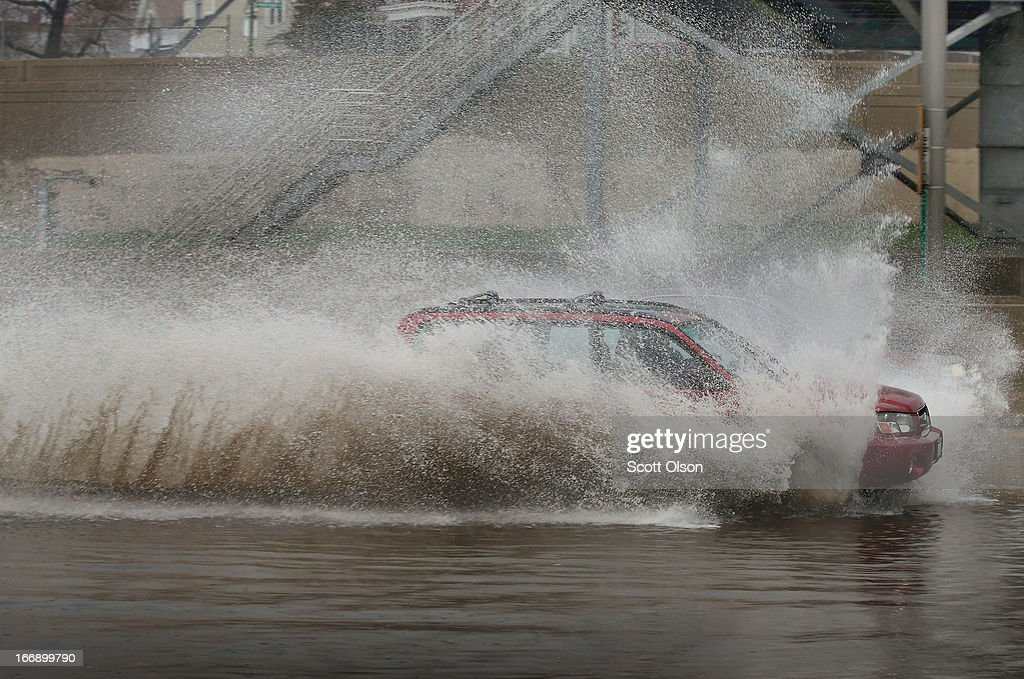 A motorist drives through a flooded section of the Kennedy Expressway on April 18, 2013 in Chicago, Illinois. Thunderstorms dumped up to 5 inches of rain on parts of the Chicago area overnight, closing sections the Edens, Eisenhower and Kennedy expressways, which lead to and from downtown, during the morning rush.