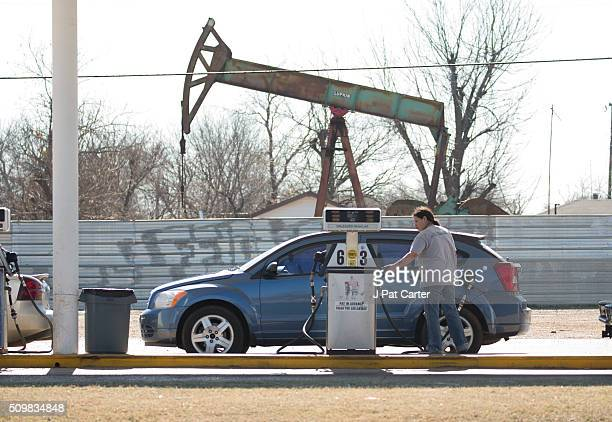 A motorist fills her car with gas at a gas station near an oil field pumping rig February 12 2016 in Oklahoma City Oklahoma Earlier this week gas...