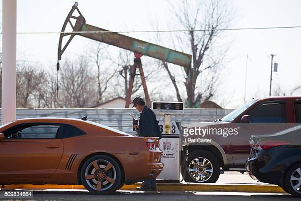 A motorist fills his car with gas at a gas station near an oil field pumping rig February 12 2016 in Oklahoma City Oklahoma Earlier this week gas...