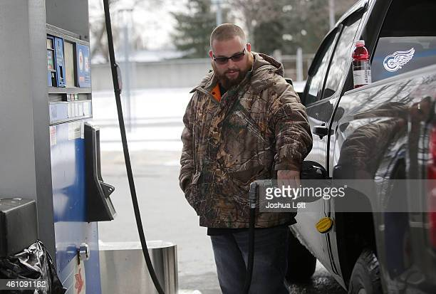 A motorist fills his vehicle with fuel at a Mobil station January 6 2015 in Livonia Michigan Crude oil dropped below $50 a barrel Tuesday making the...