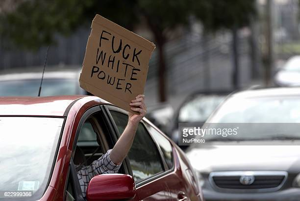 A motorist holds a sign while waiting for crowd of antiTrump protesters to pass by in Los Angeles California on November 12 2016 According to the...