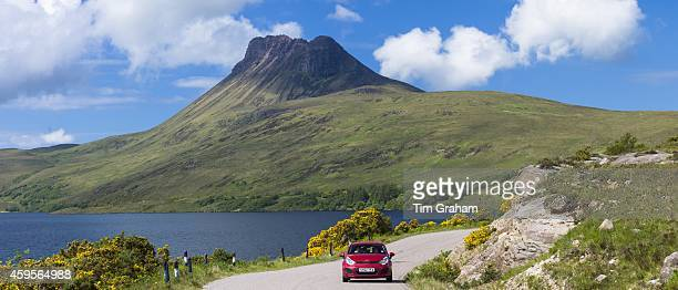 Motorist on touring holiday by Stac Pollaidh Stack Polly mountain in Inverpolly National Nature Reserve in Coigach area of North West Highlands...
