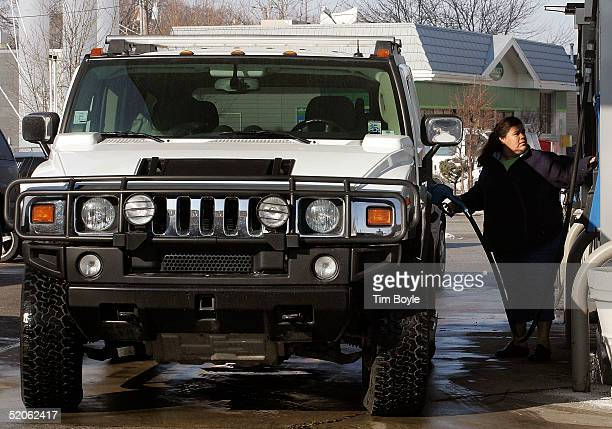 A motorist pumps gas into her Hummer SUV January 25 2005 at a Mobil gas station in Des Plaines Illinois The average price of gas has increased for...