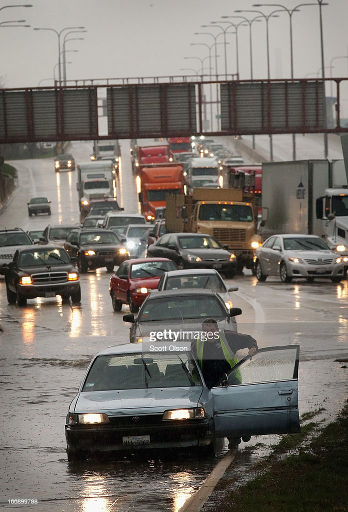 A motorist pushes his disabled car after it died while driving through a flooded section of the Kennedy Expressway on April 18, 2013 in Chicago, Illinois. Thunderstorms dumped up to 5 inches of rain on parts of the Chicago area overnight, closing sections the Edens, Eisenhower and Kennedy expressways, which lead to and from downtown, during the morning rush.