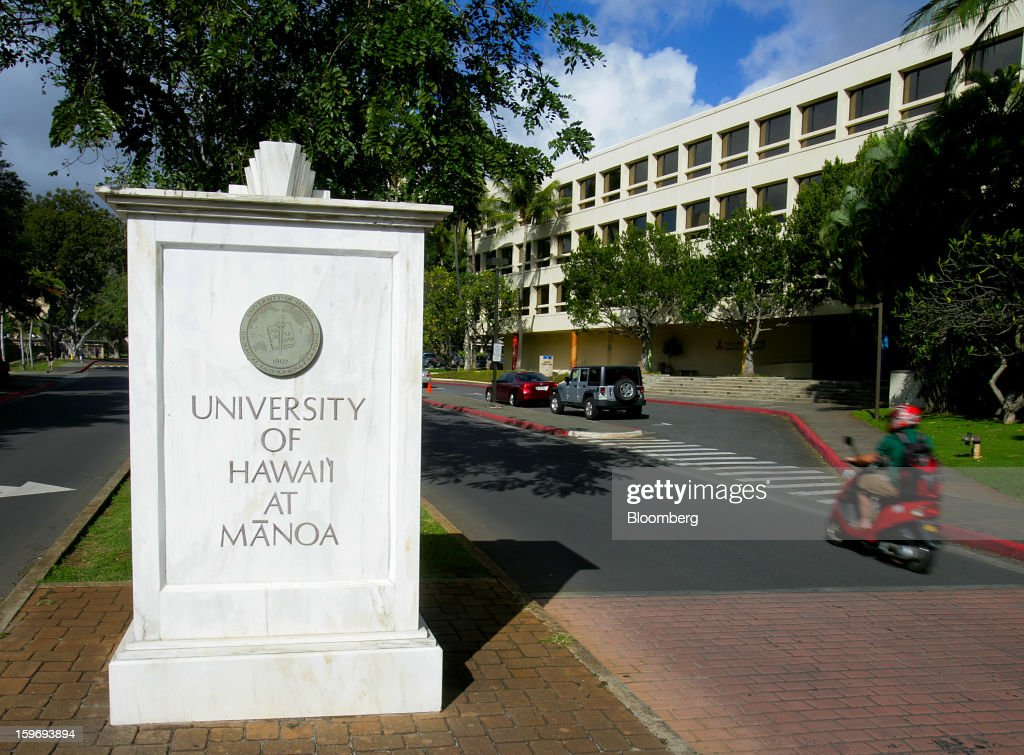 A motorist rides a scooter at the University of Hawaii in Honolulu, Hawaii, U.S., on Wednesday, Jan. 9, 2013. Honolulu, the southernmost major U.S. city, is a major financial center of the islands of the Pacific Ocean. Photographer: Tim Rue/Bloomberg via Getty Images
