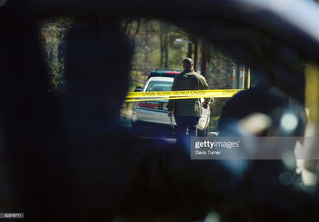 A motorist slows down to watch law enforcement officers at a crime scene at the corner of Canter Road and Lennox Road where an Atlanta customs agent...