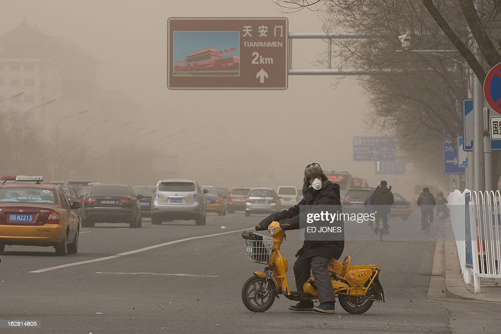 A motorist wearing a face mask waits to cross a road before a sign for Tiananmen Square during a sand storm in heavily polluted weather in Beijing on February 28, 2013. Beijing residents were urged to stay indoors as pollution levels soared before a sandstorm brought further misery to China's capital. AFP PHOTO / Ed Jones