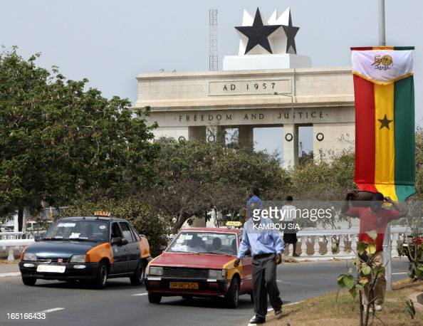 Motorists and local residents pass by the monument dedicated to the country independence in the capital city Accra 02 March 2007 ahead of the...