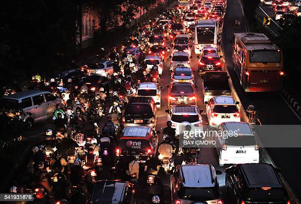 Motorists are seen in a traffic jam on a main road in Jakarta on June 21 2016 as they return home to break the fast during the holy Muslim month of...
