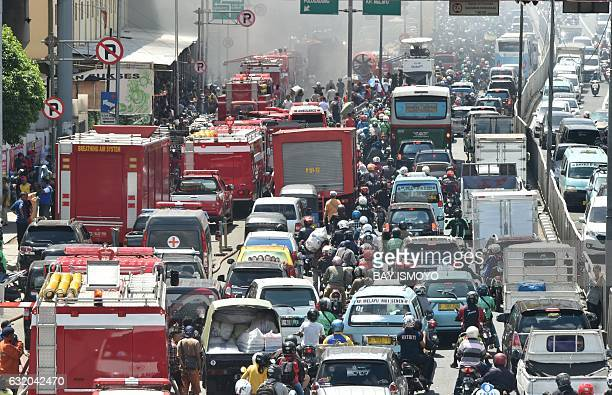 Motorists are stuck in traffic as thick black smoke rises up from kiosks on fire at one of the biggest shopping center in Jakarta on January 19 2017...