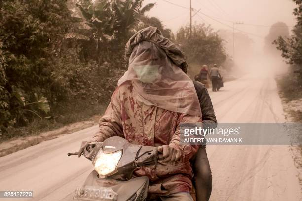 TOPSHOT Motorists cover their faces as thick ashes blankets Tiga Pancur village in Karo North Sumatra on August 2 after the Mount Sinabung volcano...