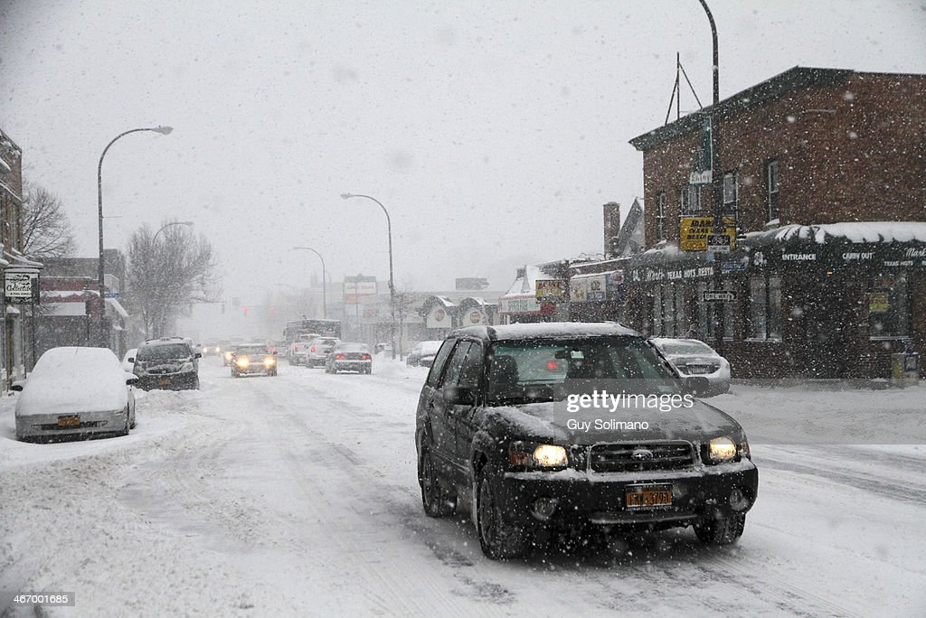Motorists drive along Monroe Avenue during a snow storm on February 5, 2014 in Rochester, New York. An additional foot of snow blanketed Western New York overnight in the latest winter storm system that has affected areas from Kansas to Maine.