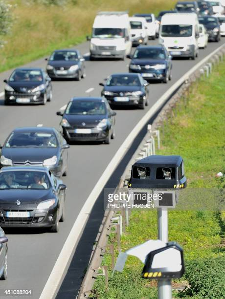 Motorists drive by a radar part of an average speed measuring system on June 23 2014 near Englos northern France This system operates as sets of two...