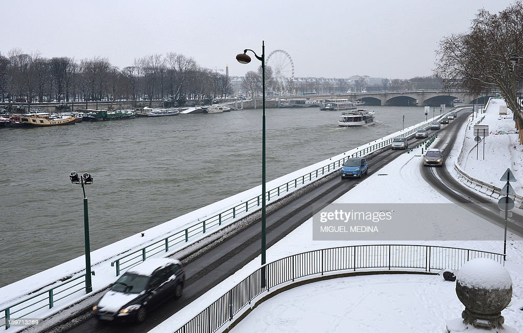 Motorists drive on the bank of the Seine river on January 19, 2013 in Paris, after the snow fell over the French capital overnight.