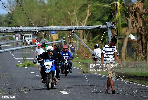 Motorists drive past downed electric posts on the national road after typhoon NockTen made landfall in Nabua Camarines Sur on December 26 2016...