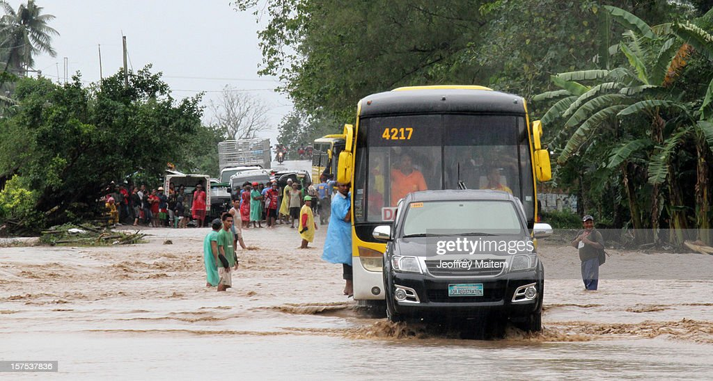 Motorists drive up a flooded highway after heavy rains and strong winds, brought about by Typhoon Bopha,l hit the township of Mabini on December 04, 2012 in the province of Compostela Valley in the southern Philippines. Typhoon Bopha made landfall in the southern Philippines earlier today, bringing heavy rain and wind gusts of 210 km/h (130mph). So far at least 40 have died and over 40,000 people have been forced into shelters.