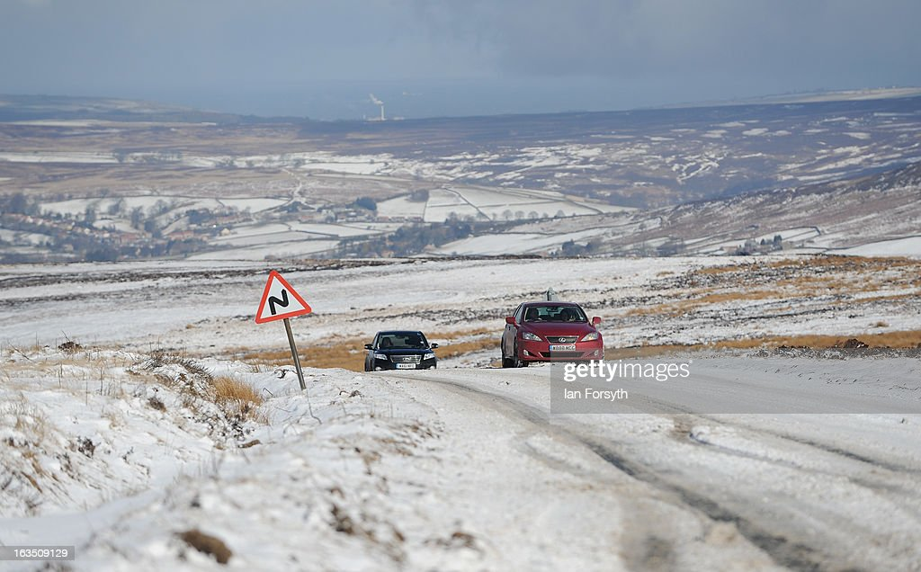 Motorists make their way across snow covered roads as brief but heavy snow storms move across the Yorkshire Moors on March 11, 2013 in Yorkshire, United Kingdom. Wintery weather returned to the UK as snow fell across many parts of the country, with a number of weather warnings being issued.