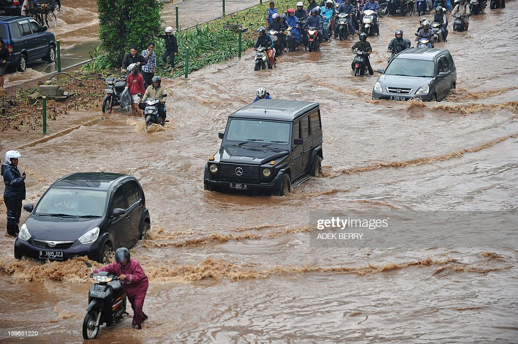 Motorists make their way through a flooded street in Jakarta on January 18, 2013. Floods in Indonesia's capital Jakarta have left at least 11 people dead, authorities said on January 18 as murky brown waters submerged parts of the city's business district, causing chaos for a second day.
