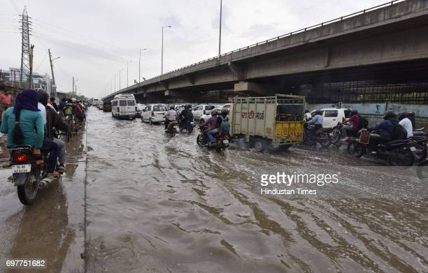 Motorists navigate a waterlogged road at Hero Honda Chowk after heavy rainfall lashed Delhi and NCR on June 19 2017 in Gurgaon India With just one...