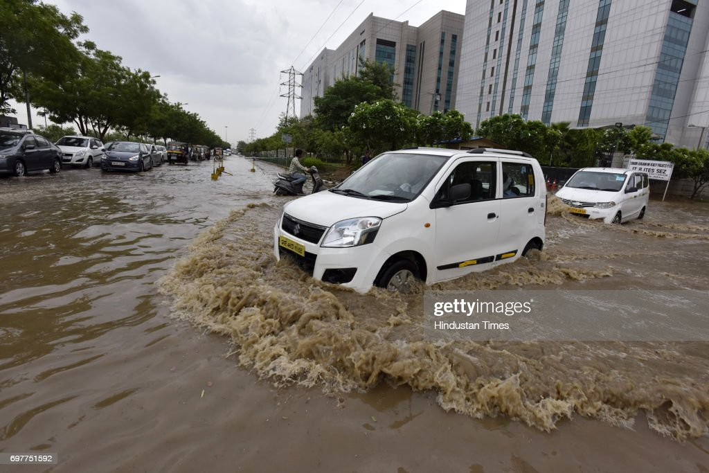 Motorists navigate a waterlogged road at Sector-48 after heavy rainfall lashed Delhi and NCR on June 19, 2017 in Gurgaon, India. With just one night of rain, several internal roads and at major intersections such as Huda City Centre, Signature Tower Road, Hero Honda Chowk and Iffco Chowk were waterlogged, delaying commuters, especially officegoers.