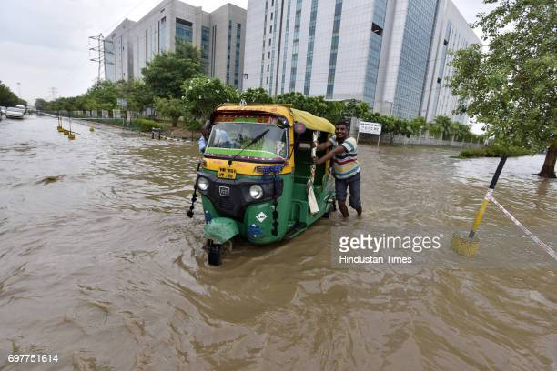 Motorists navigate a waterlogged road at Sector48 after heavy rainfall lashed Delhi and NCR on June 19 2017 in Gurgaon India With just one night of...