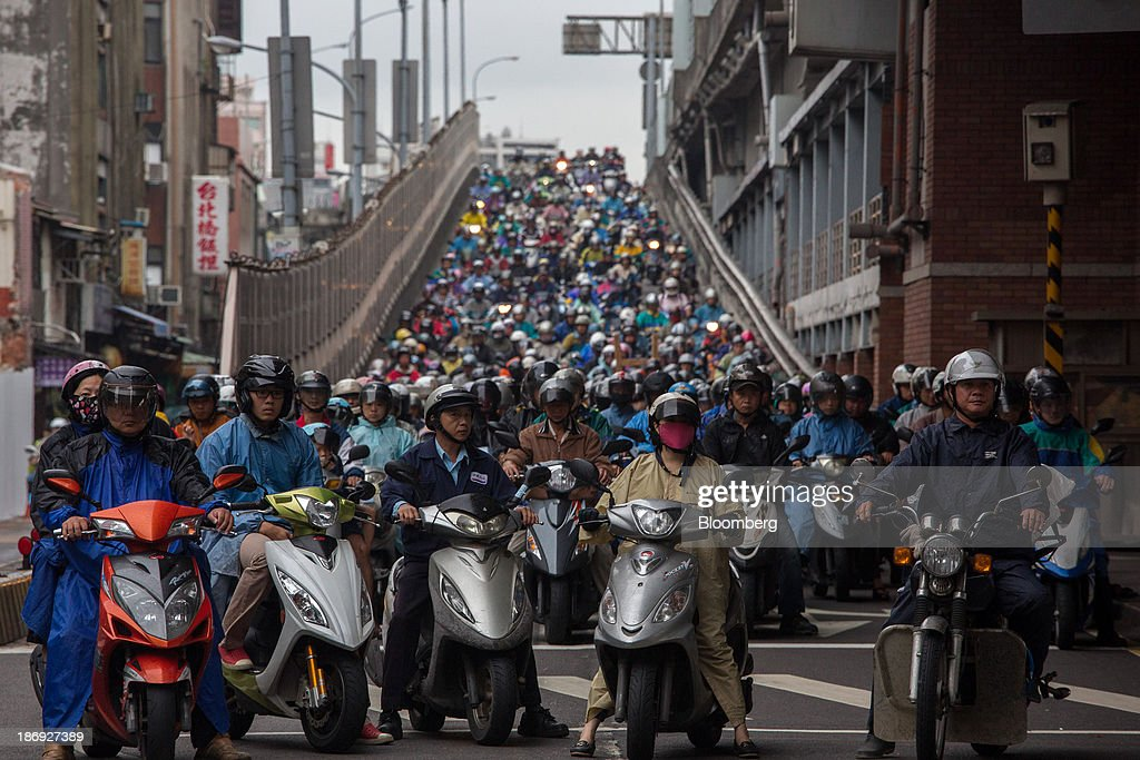Motorists on motorcycles sit in traffic along a bridge in Taipei, Taiwan, on Monday, Nov. 4, 2013. Taiwans five-year bonds gained for the first time in four days, lowering the yield from a three-week high, after a report showed inflation cooled. The local dollar strengthened. Photographer: Lam Yik Fei/Bloomberg via Getty Images
