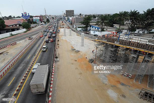Motorists on the ValeryGiscardd'Estaing boulevard drive by an interchange under construction on February 13 2014 near the Ebrie lagoon in Abidjan The...