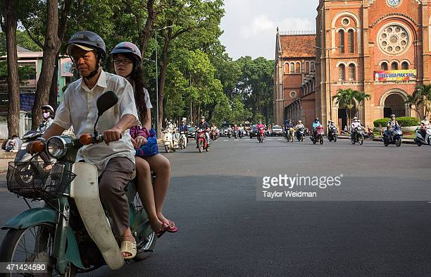 Motorists pass by the Saigon NotreDame Basilica on April 21 2015 in Ho Chi Minh City Vietnam April 30th marks the 40th anniversary of the capture of...