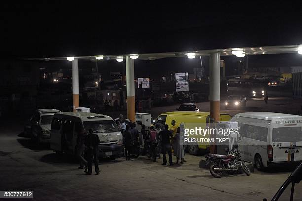 Motorists queue in the night to buy fuel at a filling station in Ibafo Ogun State southwest Nigeria on May 11 2016 Nigeria hiked the price of petrol...