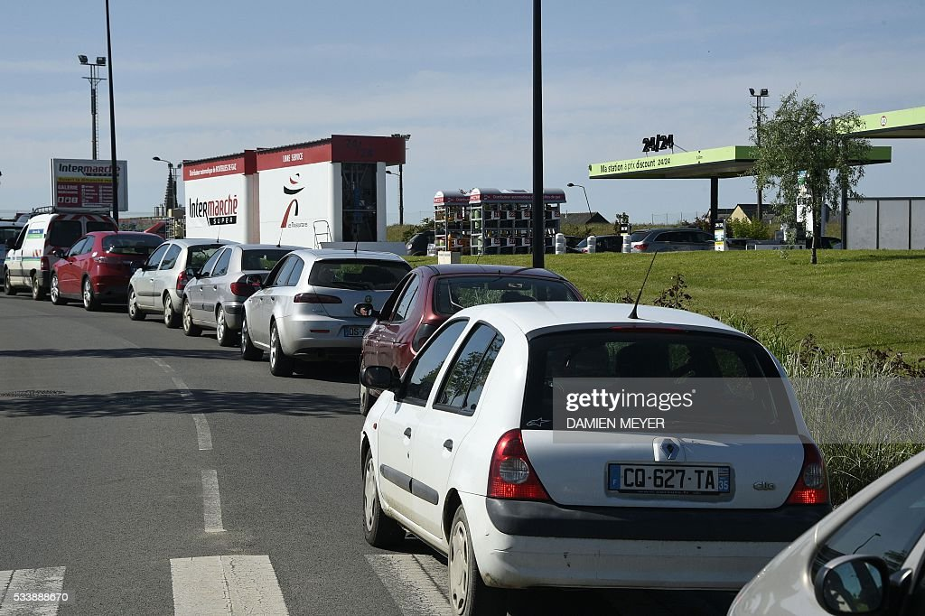 Motorists queue to refuel their vehicles at a petrol station in Combourg, western France, on May 24, 2016, following blockades of several oil refineries and fuel depots in France by protesters opposed to government labour reforms. Petrol shortages caused long tailbacks of motorists in parts of France on May 23 as protesters angry over government labour reforms blockaded some of the country's oil refineries and fuel depots. The action was the latest in three months of strikes and protests against the reform, which has set the Socialist government against some of its traditional supporters and sometimes sparked violence. MEYER