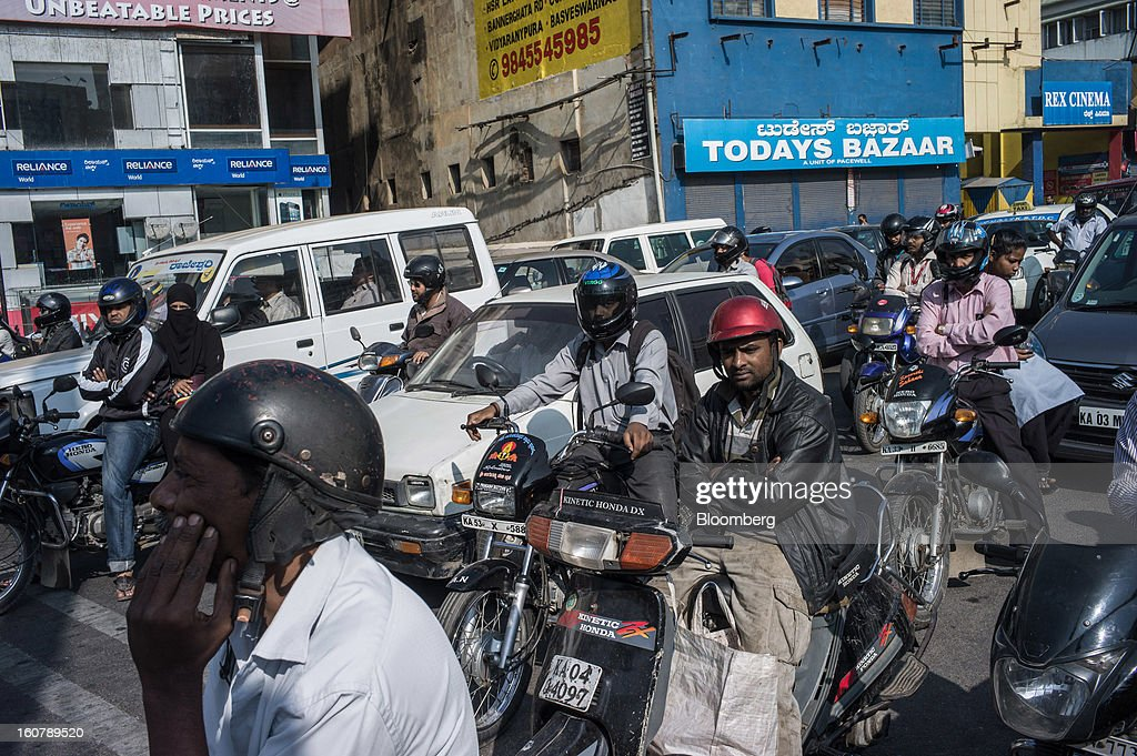 Motorists wait at a traffic stop in Bangalore, India, on Tuesday, Feb. 5, 2013. India's monetary authority predicted that the economy will expand 5.5 percent in the year ending March 31, which would be the smallest gain since 2003. Photographer: Sanjit Das/Bloomberg via Getty Images