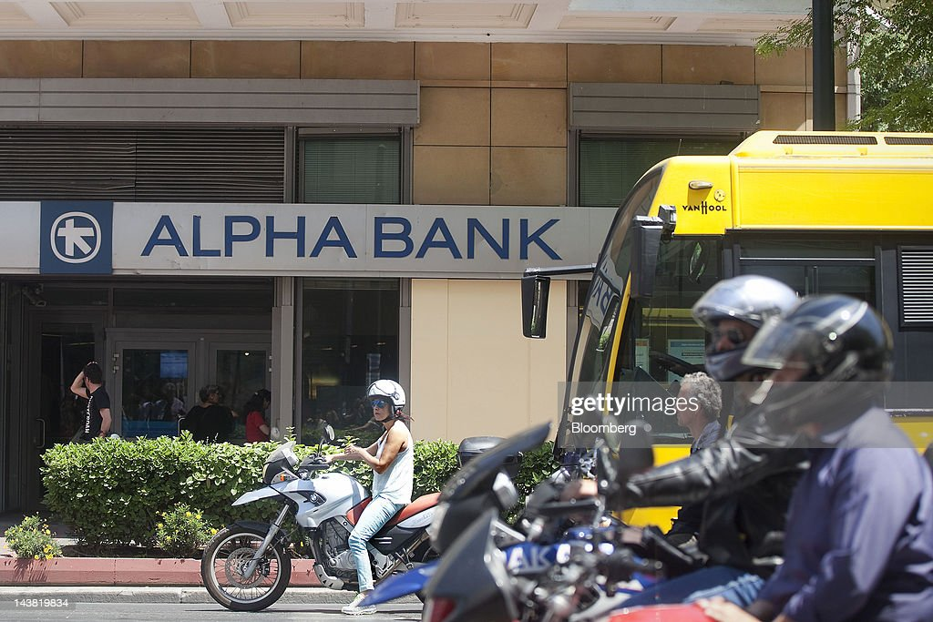 Motorists wait for a traffic signal on a road outside an Alpha Bank AE branch in Athens, Greece, on Friday, May 4, 2012. European stocks dropped as investors awaited today's American payrolls report and elections in France, Greece, Italy and Germany this weekend. Photographer: Simon Dawson/Bloomberg via Getty Images