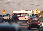 Motorists wave as police cars pursue the Ford Bronco driven by Al Cowlings carrying fugitive murder suspect OJ Simpson on a 90minute slowspeed car...