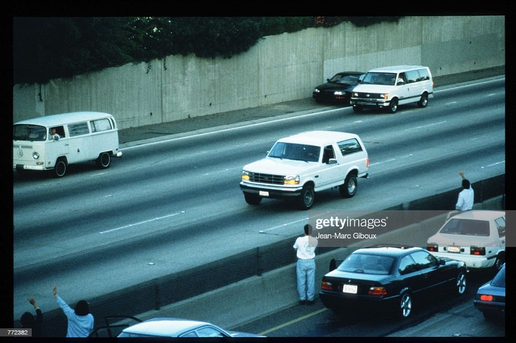 Motorists wave as police cars pursue the Ford Bronco (white, R) driven by Al Cowlings, carrying fugitive murder suspect O.J. Simpson, on a 90-minute slow-speed car chase June 17, 1994 on the 405 freeway in Los Angeles, California. Simpson's friend Cowlings eventually drove Simpson home, with Simpson ducked under the back passenger seat, to Brentwood where he surrendered after a stand-off with police.