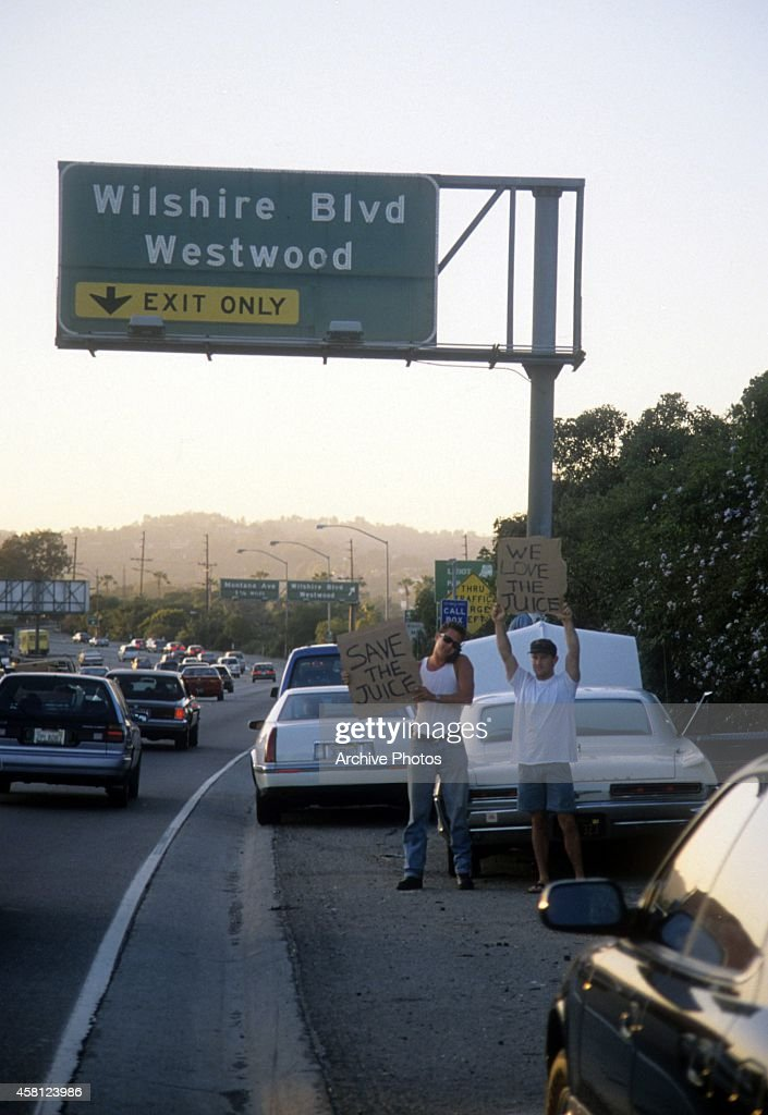 Motorists wave signs as police cars pursue the Ford Bronco driven by Al Cowlings, carrying fugitive murder suspect O.J. Simpson, on a 90-minute slow-speed car chase June 17, 1994 on the 405 freeway in Los Angeles, California. Simpson's friend Cowlings eventually drove Simpson home, with Simpson ducked under the back passenger seat, to Brentwood where he surrendered after a stand-off with police.