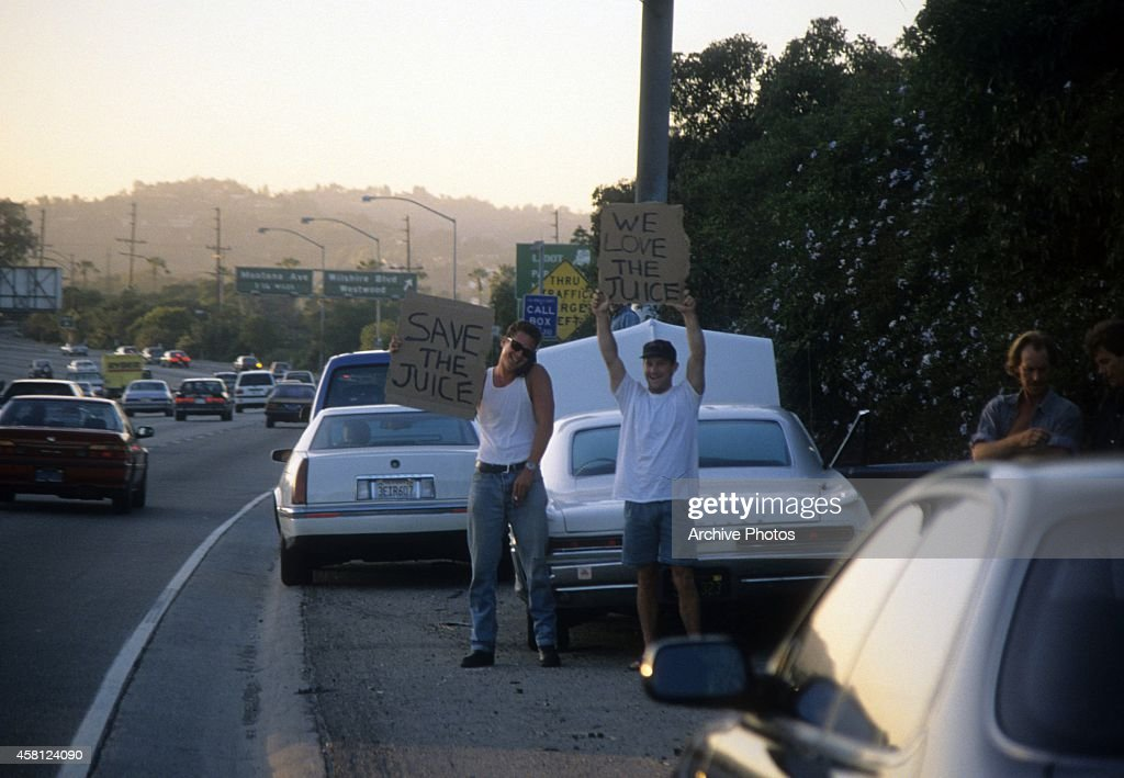 Motorists wave signs as police cars pursue the Ford Bronco driven by Al Cowlings carrying fugitive murder suspect OJ Simpson on a 90minute slowspeed...