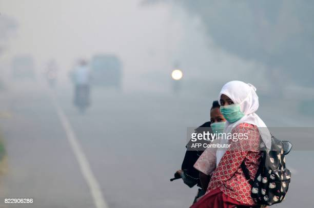 Motorists wear masks as they make their way along a road shrouded in thick smoke due to peat forest fires in Meulaboh Aceh province on July 26 2017...