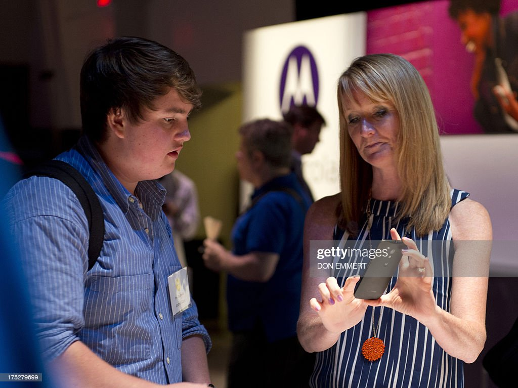A Motorola employee (R) demonstrates a Motorola's Moto X for a member of the media as the American-manufactured smartphone is unveiled August 1, 2013 at a news conference in New York. The Google-owned company said users will be able to customize a number of the parts on the Moto X, including various colors and materials such as wood. AFP PHOTO/Don Emmert