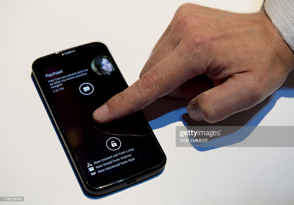 A Motorola employee demonstrates Motorola's Moto X as the American-manufactured smartphone is unveiled August 1, 2013 at a news conference in New York. The Google-owned company said users will be able to customize a number of the parts on the Moto X, including various colors and materials such as wood. AFP PHOTO/Don Emmert