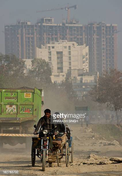 A motorrickshaw driver rides on a dirt road past buildings undergoing construction in Ghaziabad on the outskirts of New Delhi on February 27 2013...