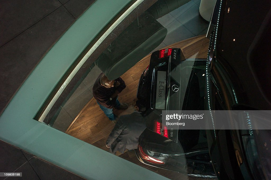 Motors Ltd. sales assistant, right, is viewed through a glass floor as he shows a Daimler AG Mercedes-Benz E-class vehicle to a customer inside the company's newly opened Mercedes-Benz India flagship dealership in New Delhi, India, on Saturday, Jan. 19, 2013. The Indian Finance Ministry projects Asia's third-largest economy will expand as little as 5.7 percent in the 12 months to March 31, which would be the weakest pace in a decade. Photographer: Sanjit Das/Bloomberg via Getty Images