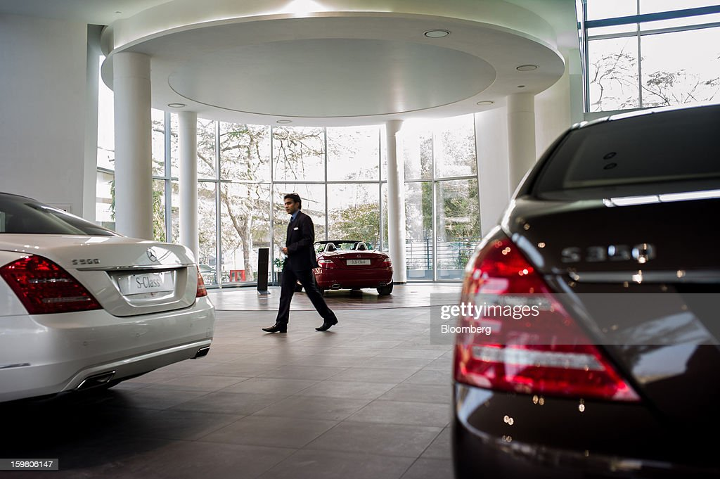 Motors Ltd. sales assistant walks past Daimler AG Mercedes-Benz S-Class vehicles displayed inside the company's newly opened Mercedes-Benz India flagship dealership in New Delhi, India, on Saturday, Jan. 19, 2013. The Indian Finance Ministry projects Asia's third-largest economy will expand as little as 5.7 percent in the 12 months to March 31, which would be the weakest pace in a decade. Photographer: Sanjit Das/Bloomberg via Getty Images