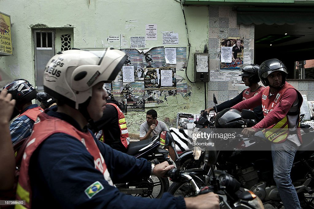 Mototaxi drivers sit parked while waiting for customers at the commercial center of the Rocinha slum in Rio de Janeiro, Brazil, on Wednesday, Nov. 28, 2012. About 56 percent of the 12 million people who live in slums like Rocinha were considered middle class in 2011, up from 29 percent in 2001, according to a study this year by Instituto Data Popular, a Sao Paulo-based research group. Photographer: Dado Galdieri/Bloomberg via Getty Images