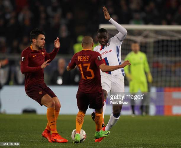 Mouctar Diakhaby of Olympique Lyonnais competes for the ball with Kevin Strootman and Bruno Peres of AS Roma during the UEFA Europa League Round of...