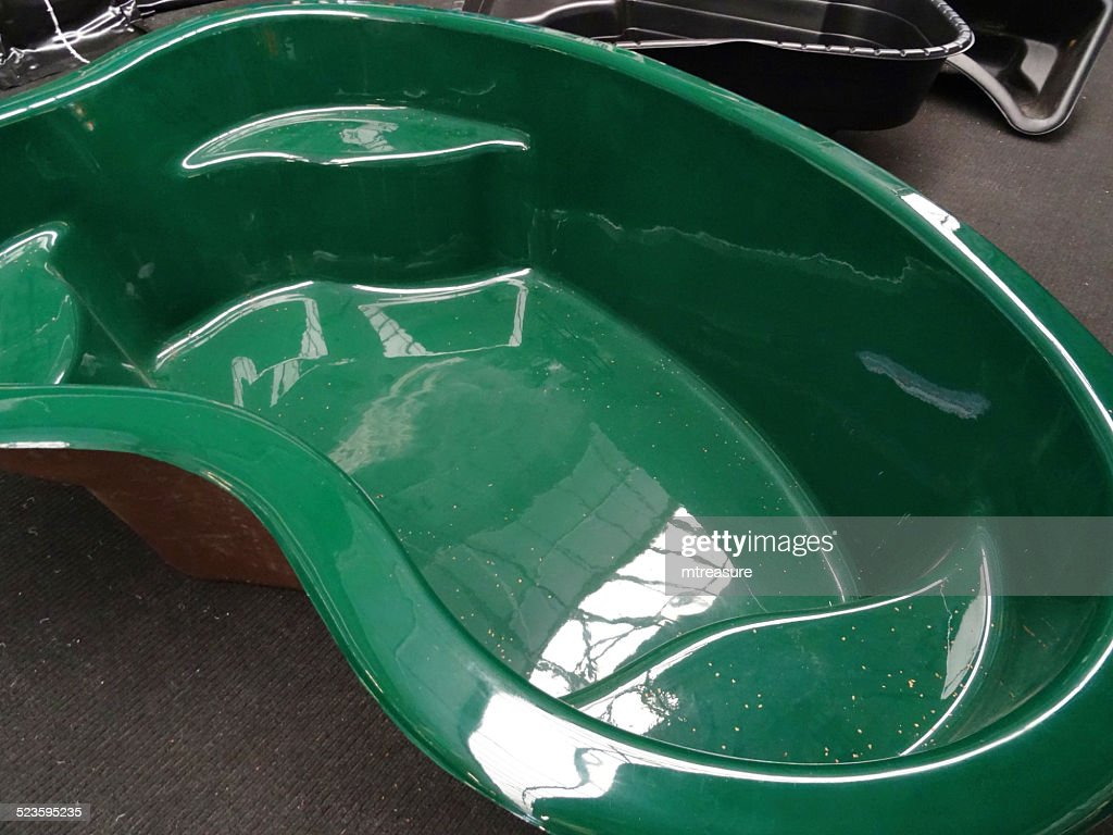 Moulded preformed green plastic garden pond highdensity polyethylene fibreglass stock photo Preformed plastic pond