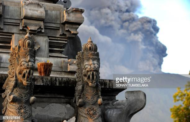 Mount Agung's eruption is seen next to a Balinese temple at Kubu subdistrict in Karangasem Regency on Indonesia's resort island of Bali on November...