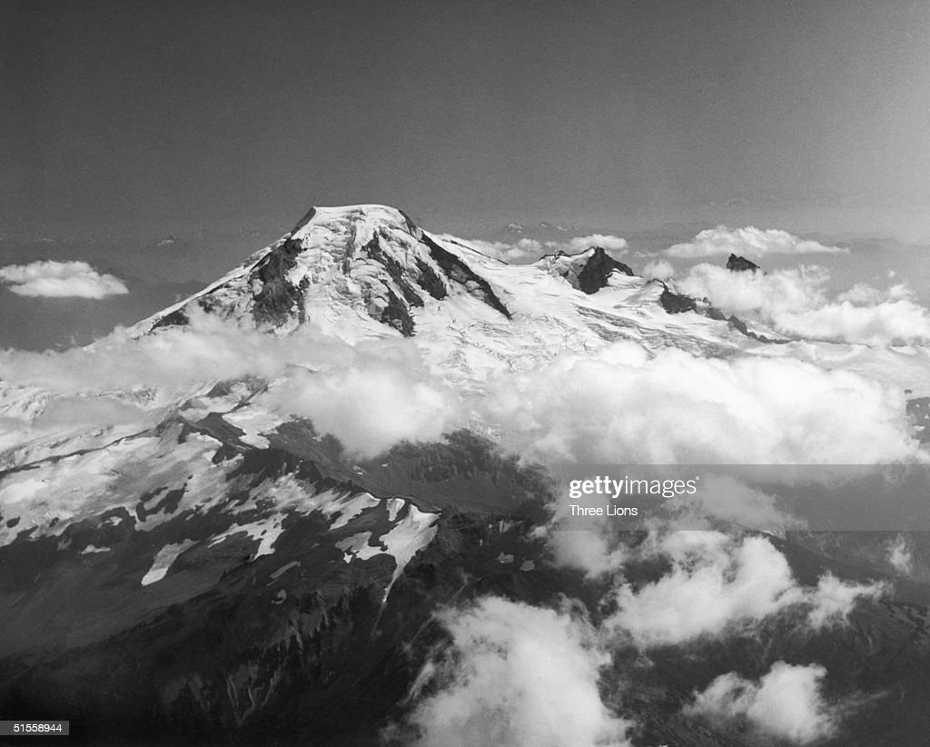 Mount Baker, a volcano of the Cascade range in Washington State, raises its head above the clouds, circa 1950.
