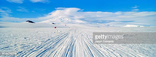 Skidoo and Hagglund vehicle trackscross the Ross Ice Shelf towards Mount Erebus an active volcano.