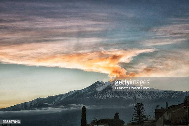 Mount Etna blowing steam at sunset